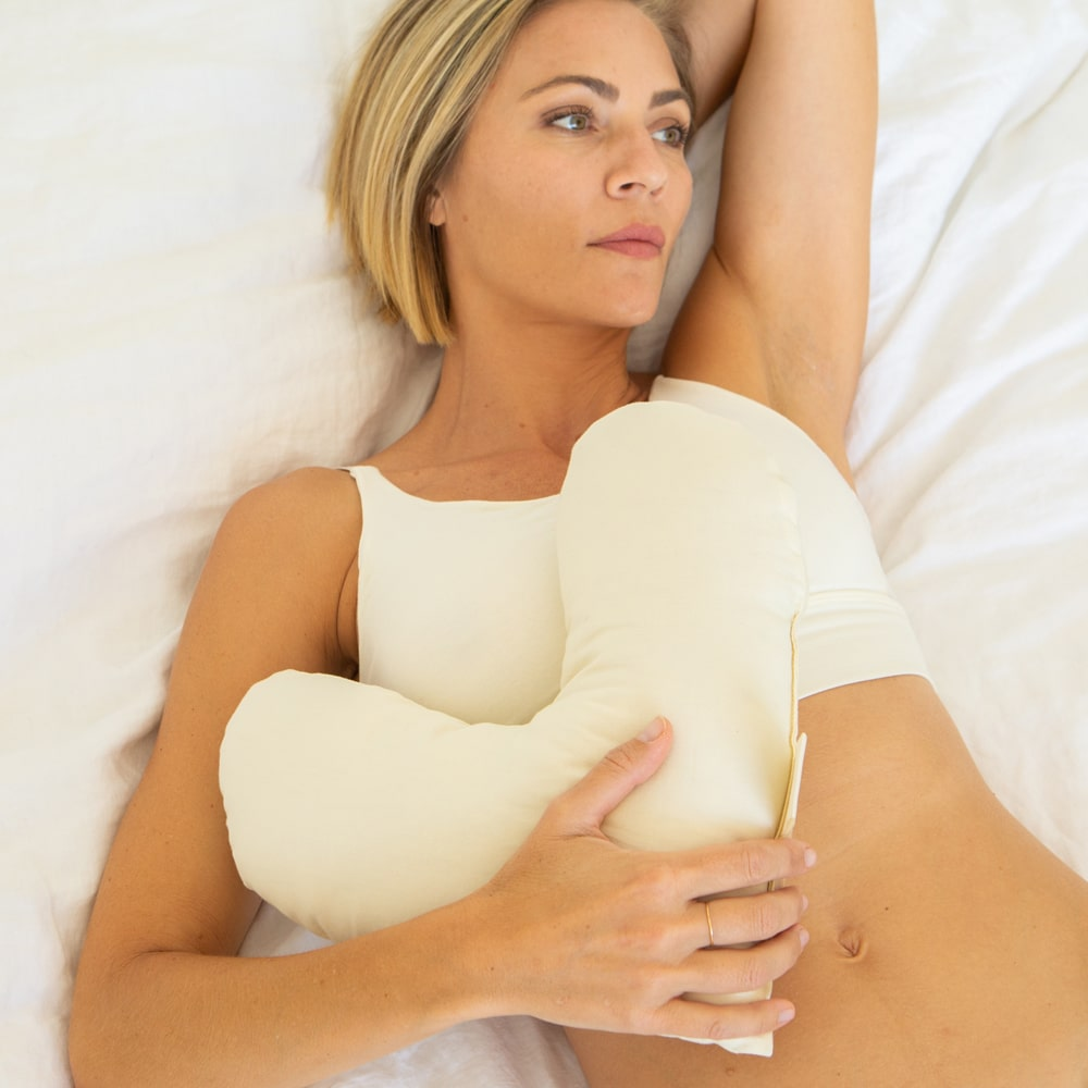 woman in bed using billow heart pillow