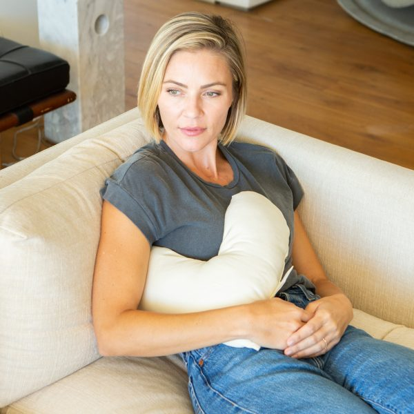 woman on couch with billow heart pillow